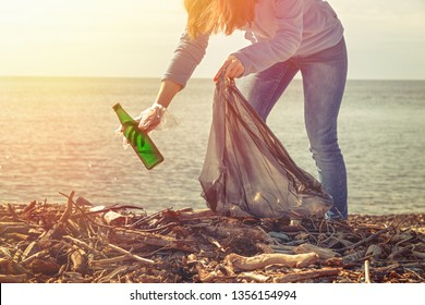 Woman volunteer helps clean the beach of trash. Earth day and environmental improvement concept. Ecology and safety for future generation. Light from the left corner.