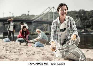 Woman volunteering. Beautiful dark-haired woman wearing squared shirt enjoying the process of volunteering cleaning the beach