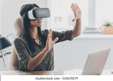Woman in VR glasses. Confident young woman in virtual reality headset pointing in the air while sitting at her working place in office