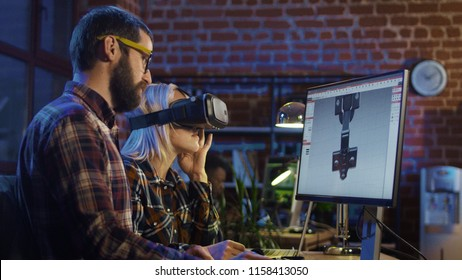 Woman in VR glasses and man sitting at computer and creating graphics of modern video game