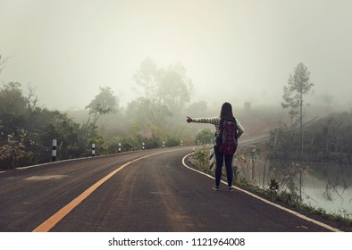 A woman is waiting for a car, on traveling alone