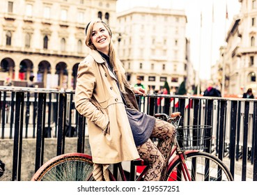 Woman waiting friends for a meeting, while she is sitting on her bicycle.