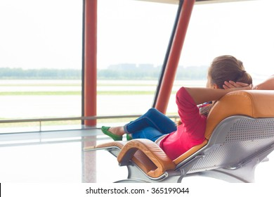 woman waiting for her flight at the airport on lounge chair
