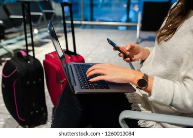 Woman waiting his flight at airport terminal, sitting on chair and typing on the laptop and smartphone.