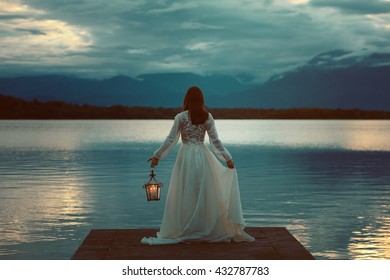 Woman waiting on a lake pier with lantern . Surreal and romantic