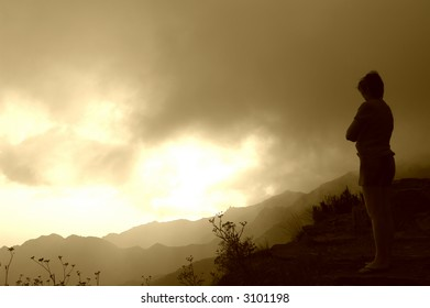 woman waiting on the mountains at sunset