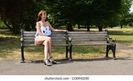 woman waiting on park bench