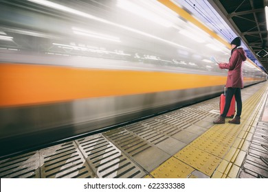 Woman waiting on the station platform and using map at the trainstation, Woman traveler to train