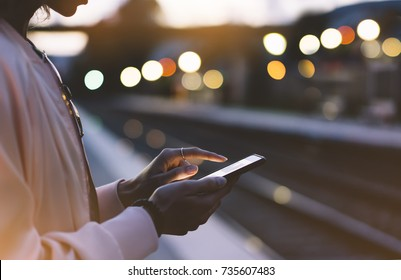 Woman waiting on station platform on background light train using smart phone in night. Tourist texting message and plan route of stop railway, railroad transport, booked. Enjoying travel concept
