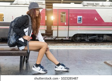 Woman waiting railway station. Traveler backpacker girl sitting on wooden bench. Asian hipster female at platform train subway traveling. Asian lady hipster photographer concept.