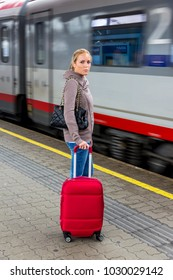 woman is waiting for train on railway station