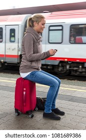 woman is waiting for train and texting