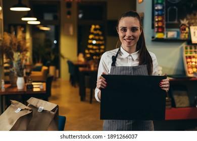 Kellnerin, die leere Tafel im Restaurant hält