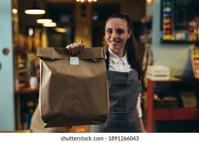 woman waitress holding take away food in restaurant