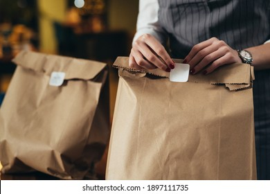 woman waitress preparing take away food in restaurant