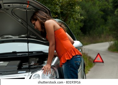 A woman waits for assistance with her car broke down on the road side, after calling for help