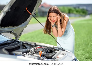 A woman waits for assistance near her car broken down on the road side.