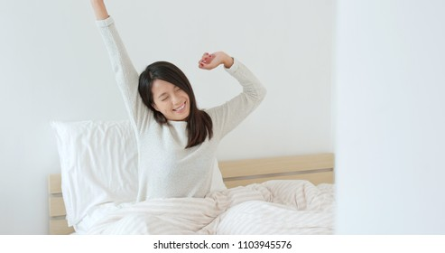 Woman wake up at morning and stretches hand on bed