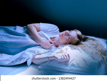 Woman wake up from night mare, looking up at moon light through the roof window.Laying in the bed with open eyes and covering with blanket.Uncomfortable bad feeling and fear in sleep