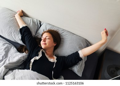 Woman waking up after sleep and stretching on bed