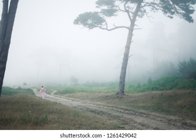 woman walk in foggy forest
