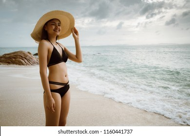 woman walk on the seaside wear a bikini wearing a sea hat, the environment bright and clear.