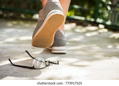 woman at the walk stepped on the glasses. unfortunate incident on the street. broken eyeglasses on asphalt