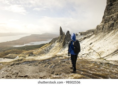 Woman walker hiker standing looking at the Old Man Of Storr on the Isle Of Skye Scotland