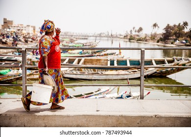 Woman walking across bridge after buying her fish for the day in St.Louis, Senegal.
