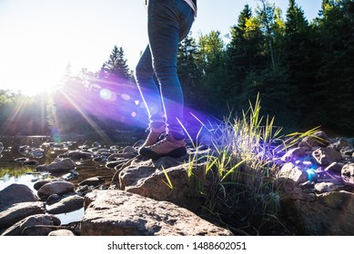 woman walking across rocks on forest stream with bright sun beams