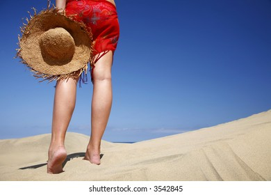 Woman walking across a sandy beach with a satraw hat