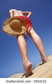 Woman walking across a sandy beach with a straw hat