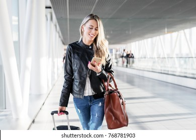 Woman walking in airport and looking at mobile phone