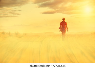 A woman is walking alone in the desert on a beautiful foggy morning desert dunes in the background,above are beautiful clouds and the rising sun.