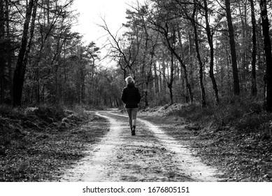 woman walking alone in the forest, social distancing in the netherlands, Hoog Soeren De Veluwe Netherlands 17 march 2020