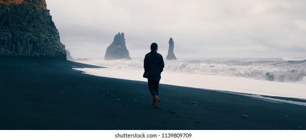 Woman walking alone on black sand beach at Reynisfjara, Iceland.