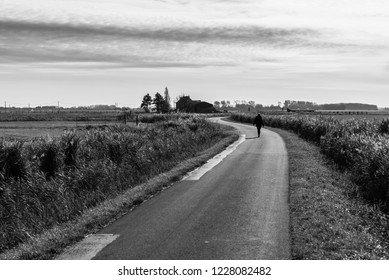 Woman walking alone on a countryroad through the meadows of the polders in Uitkerke, Blankenberge, Belgium.