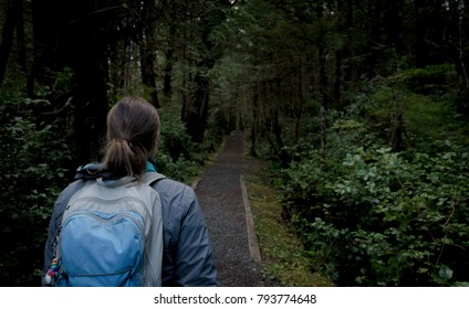 Woman walking alone on dark forest path at night