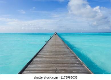 Woman walking alone on the long pier in Maldives.