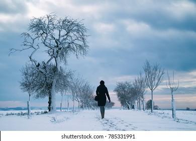 woman walking alone in winter landscape in moody weather, hiking girl in snowy landscape with dark skyline