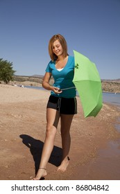 A woman walking along the beach holding on to her green umbrella with a smile on her face.