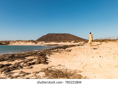 Woman walking along the beach in Isla de Lobos with mountain in the background