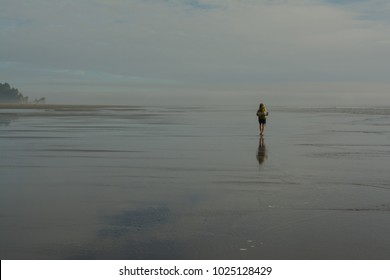 Woman walking along the coast of Olympic National Park on a backpacking trip.