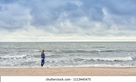 Woman walking along the edge of the surf on a beach in a blue denim outfit looking out to sea on a cold cloudy day with copy space