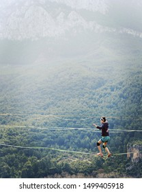 A woman is walking along a stretched sling. Highline in the mountains. Woman catches balance. Performance of a tightrope walker in nature. Highliner on the background of valley.
