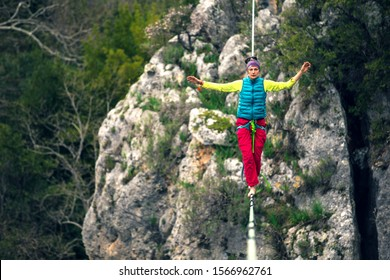 A woman is walking along a stretched sling. Highline in the mountains. Woman catches balance. Performance of a tightrope walker in nature.