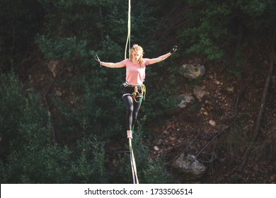 A woman is walking along a stretched sling over a forest, Highliner balances over the abyss, Highline in Turkey, Purposeful girl goes to the goal.