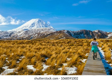 A woman walking along the Tama Lakes trail on a clear, sunny winter day. It is one of the many trails in the Tongariro National Park, New Zealand.