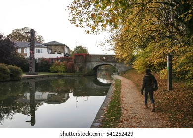 woman walking along the towpath of the grand union canal near berkhamsted castle in autumn in hertfordshire uk