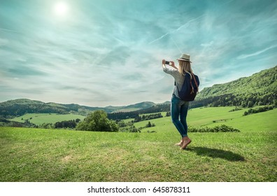 Woman walking around the mountains with her phone and shootinh beautiful green fields view under sunlight on summer day.